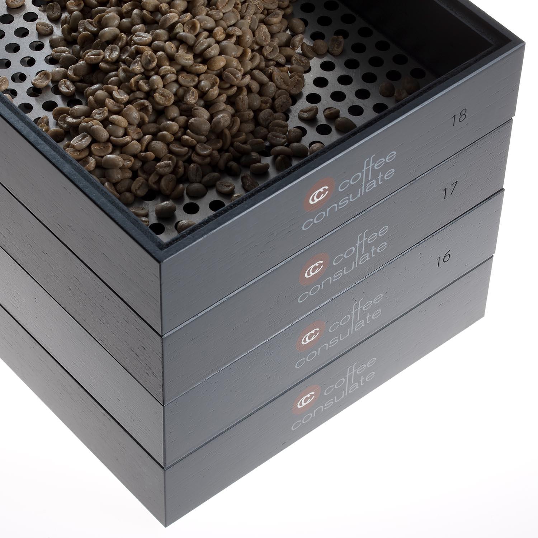 Vier Ebenen eines Screeningsets für Rohkaffee. In der oberen ebene befinden sich Kaffeebohnen.
